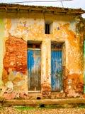 对在锁着的花格后的退色的蓝色门在砖墙上与 库存照片