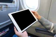 对在飞机的数字式片剂的妇女用途 库存照片