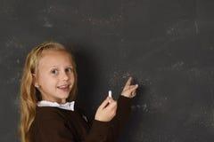 对在黑板微笑的制服的美丽的白肤金发的甜女小学生白垩文字负愉快 库存图片