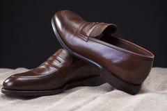 对在滤网表面安置的布朗时髦的皮革便士游手好闲者鞋子 库存图片