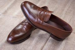 对在滤网表面安置的布朗时髦的皮革便士游手好闲者鞋子 免版税库存照片