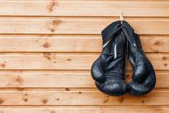 对垂悬在土气木墙壁的拳击手套 免版税库存照片