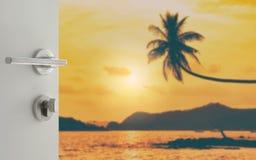 对垂悬在热带海滩的被弄脏的椰子树的被打开的白色门 免版税库存图片