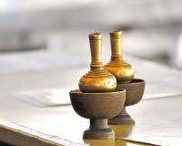对填装的水的黄铜瓶子在泰国寺庙 免版税图库摄影