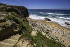 对多岩石的海滩的台阶与沙子和波浪自白天 免版税图库摄影