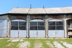 对大老火车站修理车间的入口有长得太大的火车的跟踪导致前门 免版税库存图片