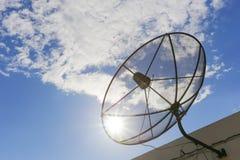对天空的卫星盘在与微小的云彩的蓝天背景中 库存图片