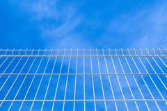 对天空的白色工业篱芭 库存图片