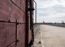 对奥斯威辛比克瑙纳粹集中营的大门,显示其中一辆运畜拖车用于给他们的死亡带来受害者 免版税库存图片