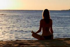 对女子瑜伽的前莲花凝思海边 免版税库存图片