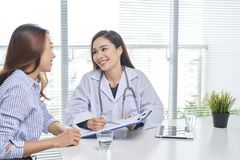 对女性患者的女性医生谈话在医院办公室 免版税图库摄影