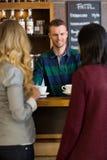 对女性朋友的年轻侍酒者服务咖啡 免版税库存照片