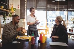 对女服务员的少妇预定的食物,当坐与男性朋友时 免版税库存图片