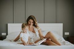 对她微笑的小男孩的年轻母亲阅读书 免版税图库摄影