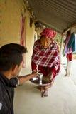 对她的丈夫的Tharu妇女提供的茶, Bardia,尼泊尔 免版税库存照片