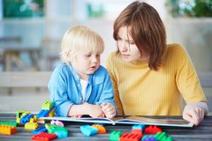 对她的儿子的年轻母亲阅读书 图库摄影
