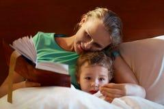 读对她的孩子的年轻母亲在床上 免版税库存图片