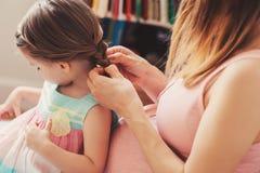 对她的小孩女儿的怀孕的母亲织法辫子在家 免版税库存图片