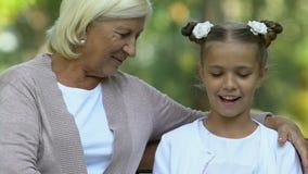 对她的更老的保姆的年轻逗人喜爱的女孩看书,坐长凳,家庭作业 股票视频