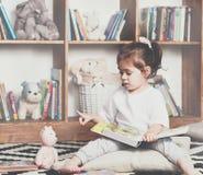 对她的玩具的逗人喜爱的情感小女孩阅读书 免版税库存照片