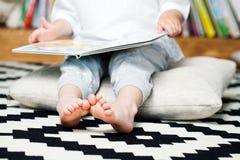 对她的玩具的逗人喜爱的情感小女孩阅读书 免版税库存图片