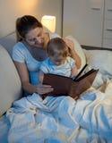 对她的男婴的美好的微笑的母亲读书真相前面是 免版税库存照片