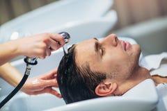 对她英俊的客户的美发师洗涤的头发 图库摄影