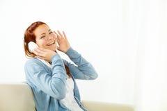 对妇女年轻人的愉快的听的音乐 免版税库存图片