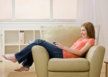 对妇女年轻人的扶手椅子听的MP3播放器 免版税图库摄影