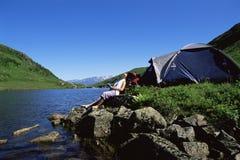 对妇女年轻人的湖下个松弛岩石 免版税库存图片