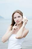 对妇女年轻人的美丽的听的贝壳 免版税库存图片