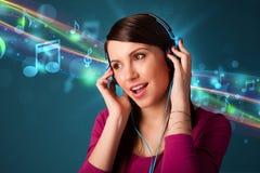 对妇女年轻人的耳机听的音乐 图库摄影