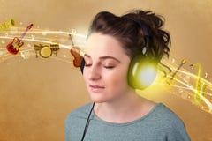 对妇女年轻人的耳机听的音乐 免版税库存照片