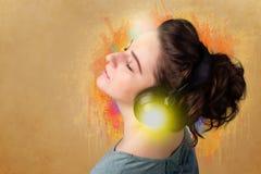 对妇女年轻人的耳机听的音乐 库存照片