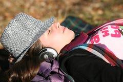 对妇女年轻人的耳机听的音乐 库存图片