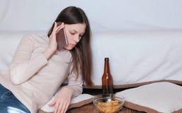对妇女的令人不快的交谈电话的 她吃芯片 免版税库存图片