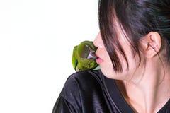对妇女的绿色金刚鹦鹉鸟宠物亲吻 免版税库存照片