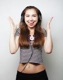 对妇女年轻人的听的音乐 愉快和耳机 免版税库存图片