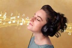 对妇女年轻人的耳机听的音乐 免版税图库摄影