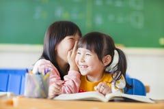 对姐妹的逗人喜爱的小女孩耳语 免版税库存图片