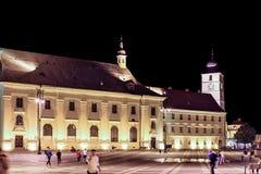 对委员会塔的夜视图和与人的大正方形 免版税库存照片