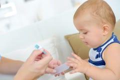 对婴孩的测量的温度 图库摄影
