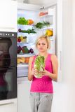对嫩卷心菜,冰箱的女孩不快乐的神色 免版税库存照片
