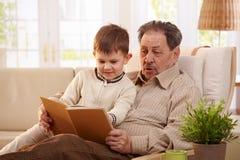 对孙子的祖父阅读书 免版税库存图片