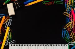 对学校用品背景的顶视图与夹子、铅笔、橡皮擦和notpad被排行的页  免版税库存图片