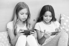 对孩子乐趣的申请 互联网冲浪和缺席父母亲情况通知 智能手机上网 女孩姐妹穿戴 库存照片