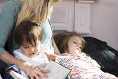 对孩子的疲乏的母亲阅读书 库存照片