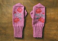对孩子的自创羊毛桃红色手套木后面的 库存照片