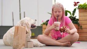 对宠物的爱-有非洲猪尾的美丽的时尚女孩在有她的狗的街道上吃 股票录像