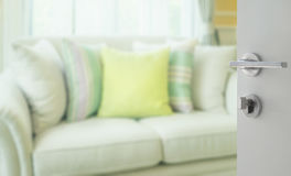 对客厅的被打开的白色门有在现代沙发的绿色枕头的 免版税库存图片